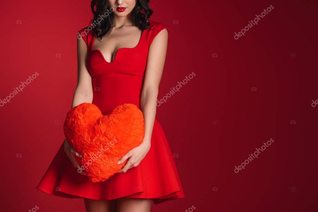 cropped image of attractive girl in red dress holding heart shaped pillow isolated on red