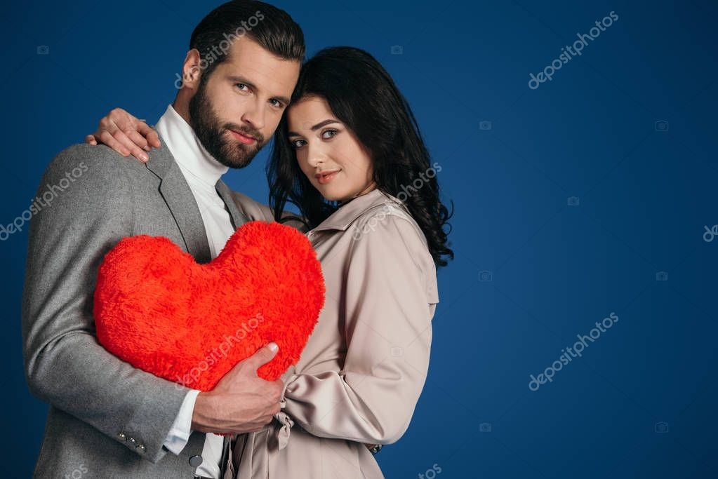 attractive couple holding heart shaped pillow isolated on blue
