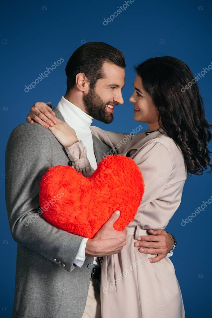 happy smiling couple holding heart shaped pillow isolated on blue