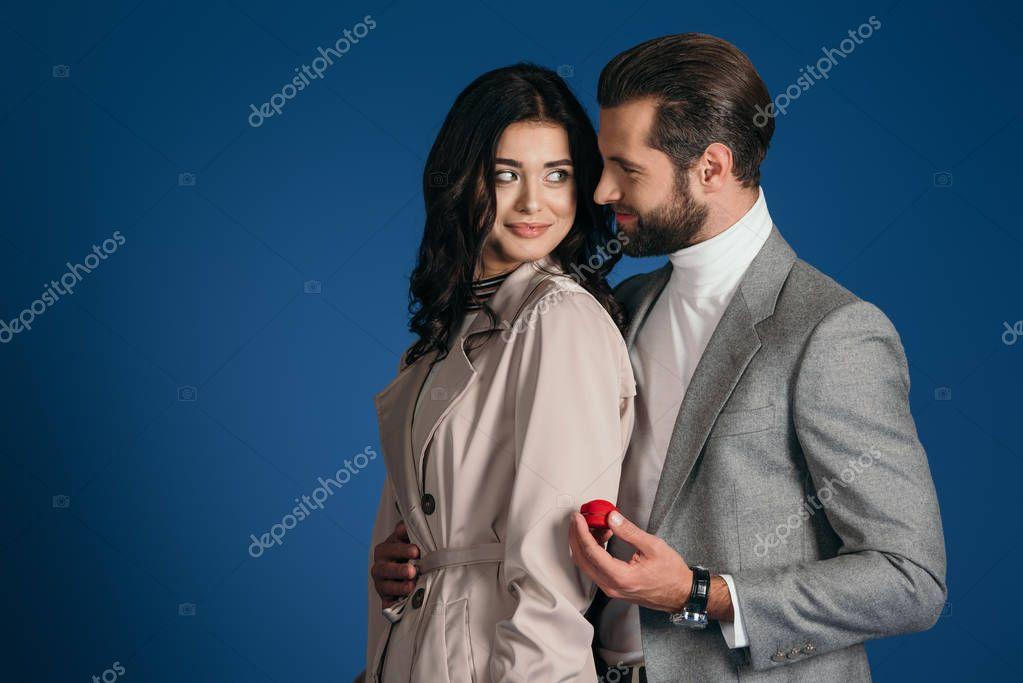 boyfriend making proposal to girlfriend isolated on blue