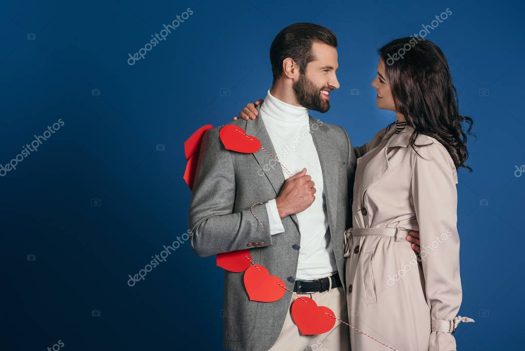 happy couple holding garland of red hearts isolated on blue