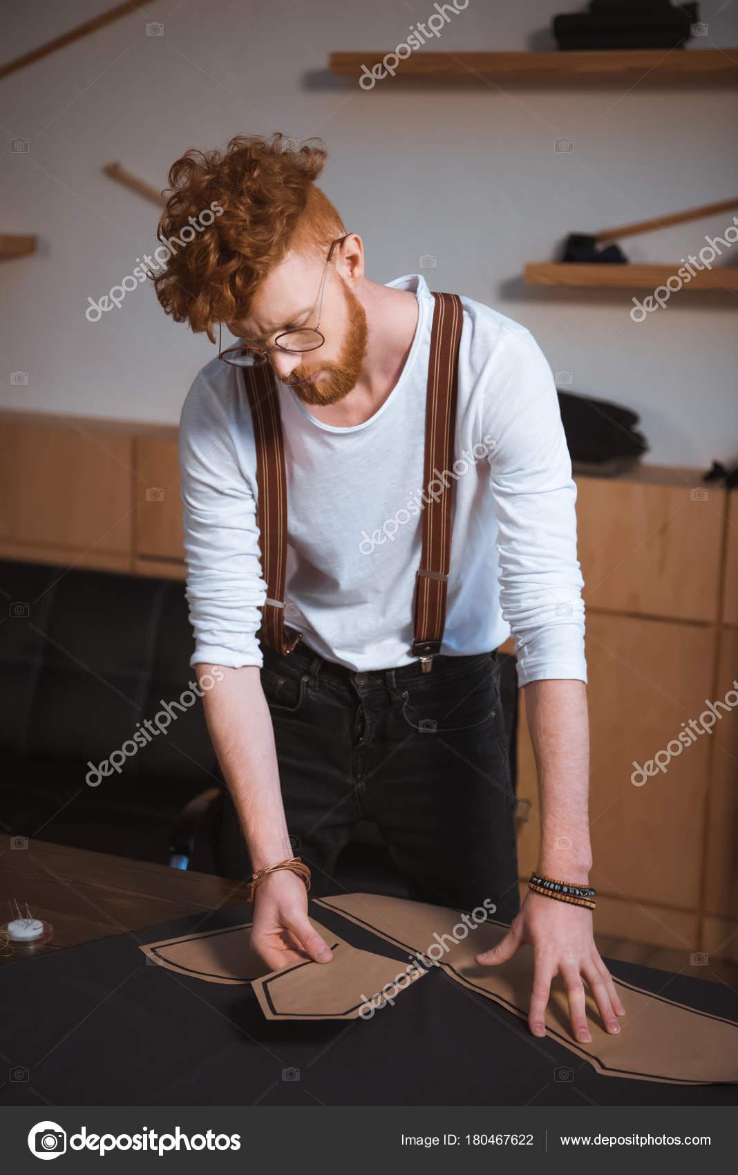 Jeune designer de mode masculine en lunettes travaillant avec le tissu et  les motifs de couture — Image de VitalikRadko c7e0a43b5729
