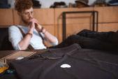 vista ravvicinata dei modelli di cucito, con strumenti di cucito e pensoso stilista maschio seduto dietro in tessuto