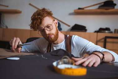 focused young bearded fashion designer working with fabric at workshop