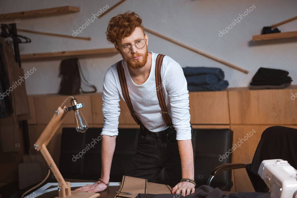 Handsome young fashion designer in eyeglasses leaning at table with sewing tools in workshop