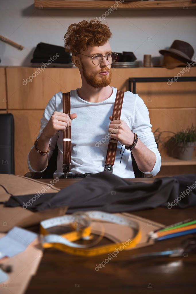 Pensive young bearded fashion designer in eyeglasses looking away while sitting at workplace