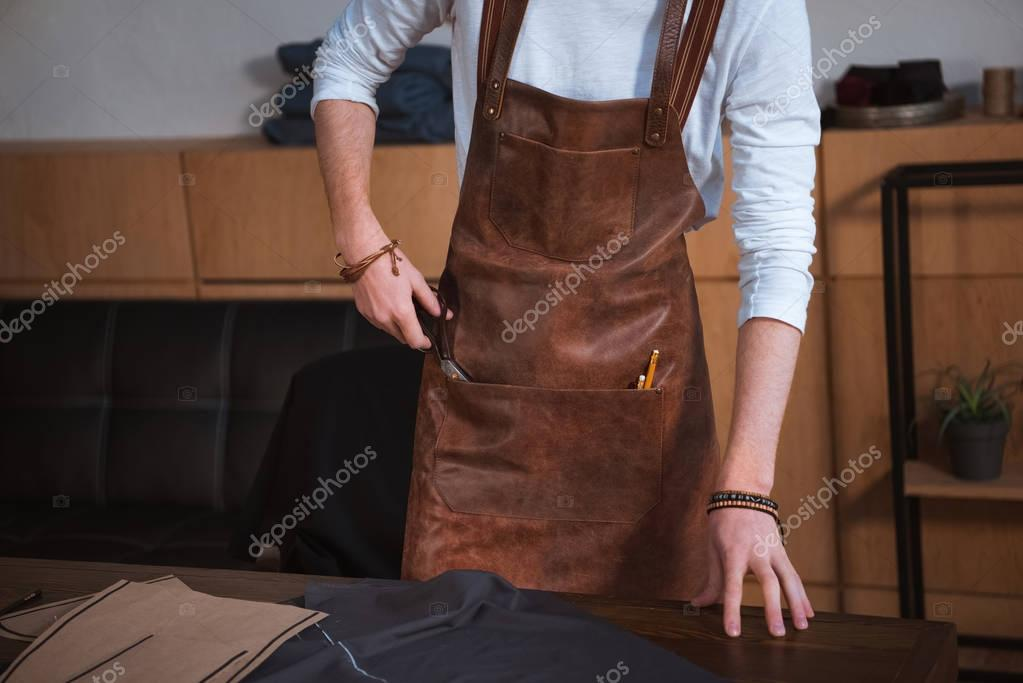 partial view of male fashion designer in apron working with sewing tools and fabric at workshop