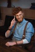 Fotografia uomo bello giovane rossa in occhiali ne su smartphone e sorridente