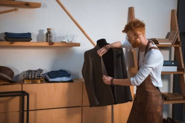 young male fashion designer in apron and eyeglasses looking at suit jacket on mannequin at workshop