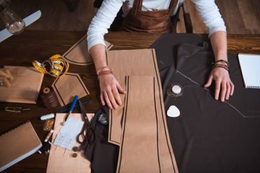 Cropped shot of male fashion designer working with sewing patterns, tools and fabric at workplace stock vector