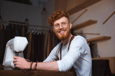 handsome smiling young fashion designer working with sewing machine