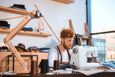 bearded young fashion designer working with sewing machine at workshop