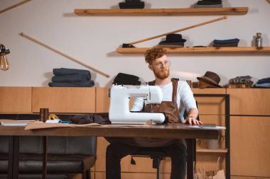 handsome young fashion designer in eyeglasses looking away while working with sewing machine in workshop