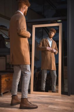stylish young man wearing overcoat and looking at mirror in boutique