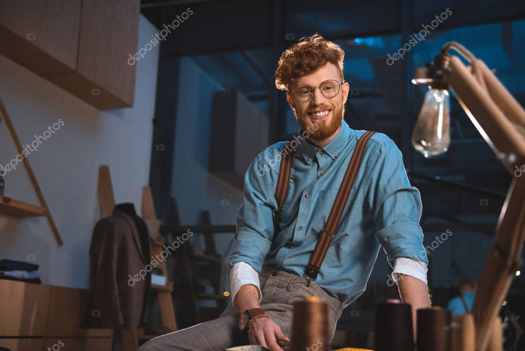 Smiling young fashion designer in eyeglasses sitting on table at workplace