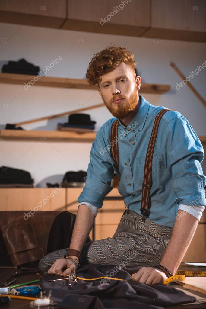 Handsome young fashion designer looking at camera while sitting on table at workplace