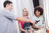 Muž, nalil víno do sklenic multikulturní přátel