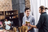 Photo men clinking with glasses of beer in kitchen