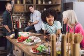 mnohonárodnostní dívky povídají v kuchyni s vínem a kamarády při pohledu na ně