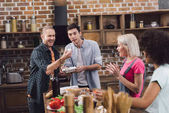Fotografie multiethnic friends playing with chicken eggs in kitchen