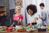 smiling multiethnic girls cooking in kitchen