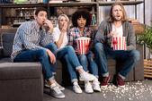 Photo Shocked multiethnic friends watching horror movie with popcorn