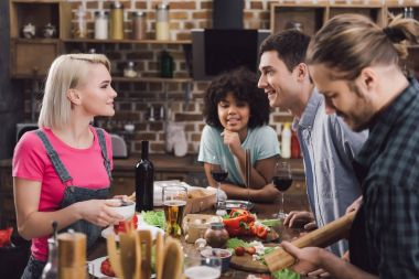 multiethnic friends talking and cooking at kitchen