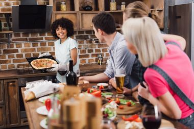 smiling african american girl bringing homemade pizza to friends