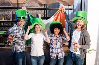 multiethnic friends celebrating saint patrick day at home