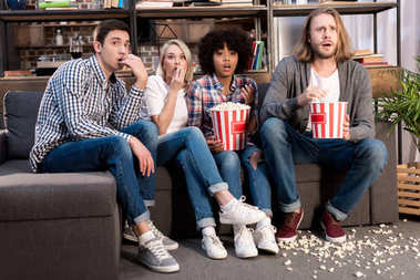 Shocked multiethnic friends watching horror movie with popcorn