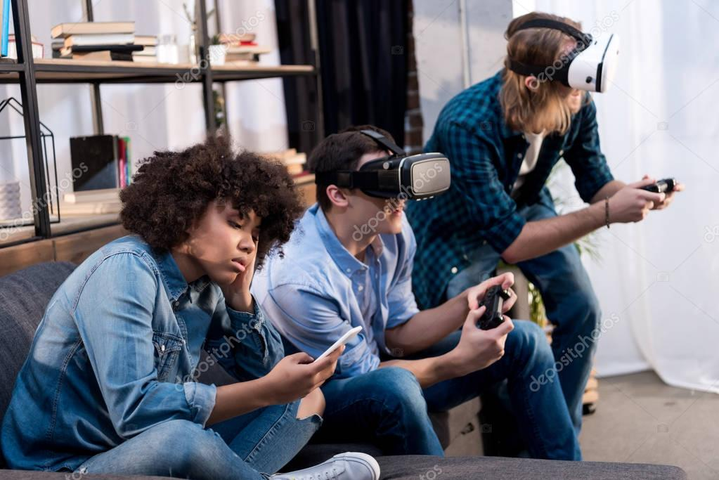 friends playing video game with virtual reality headsets, african american girl sitting with smartphone