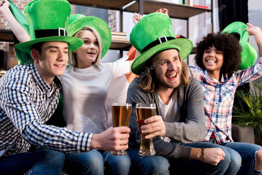 multicultural friends watching tv and clinking glasses, saint patrick day concept