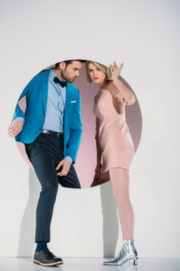 fashionable couple in love stepping through hole on grey