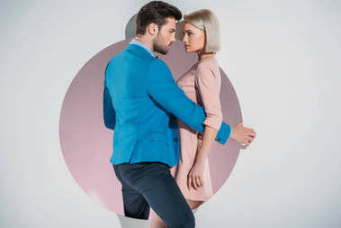 beautiful stylish young couple looking at each other while standing on hole on grey