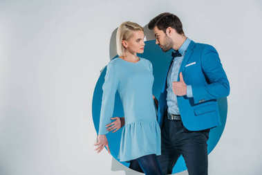 beautiful fashionable young couple looking at each other while standing in blue aperture on grey