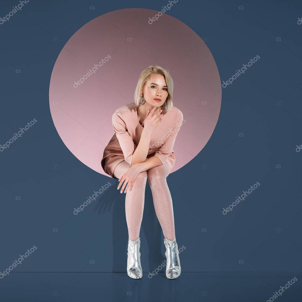 Beautiful stylish blonde girl sitting in hole and looking at camera on blue stock vector