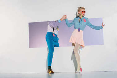 stylish young couple with colorful tags on clothes walking through opening on grey