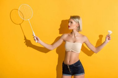 beautiful young blonde woman holding badminton racket and shuttlecock on yellow