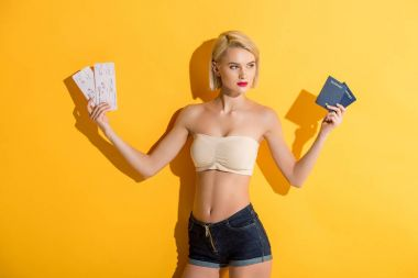 Beautiful young blonde woman in denim shorts and top holding passports and tickets on yellow stock vector