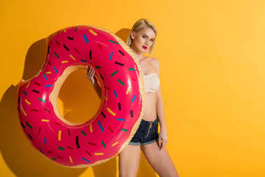 beautiful young blonde woman in denim shorts and top holding float ring and looking at camera on yellow