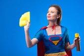 Fotografie portrét krásné superwoman s hadr a saponát pro čištění, izolované na modré