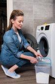 Seitenansicht der attraktiven Hausfrau, die zu Hause Wäsche wäscht