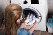 Fotografie Rückansicht der Hausfrau, die zu Hause Wäsche aus der Waschmaschine holt