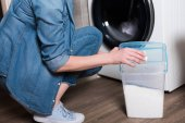 Fotografie abgeschnittene Aufnahme von Hausfrau beim Wäschewaschen zu Hause