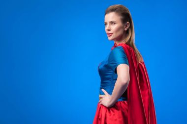 side view of beautiful woman in superhero costume standing akimbo isolated on blue