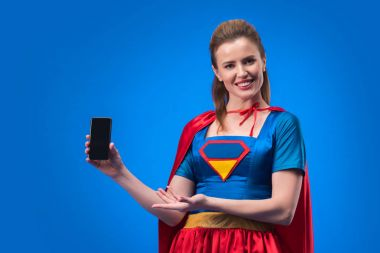 portrait of smiling woman in superhero costume showing smartphone with blank screen isolated on blue