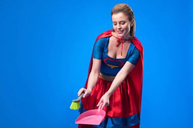 portrait of woman in superhero costume with broom and scoop for cleaning isolated on blue