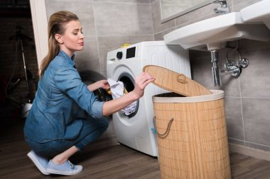 housewife putting clothing into washing machine at home