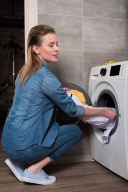 housewife taking out laundry from washing machine at home