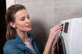 boční pohled atraktivní hospodyňka provozní pračku doma